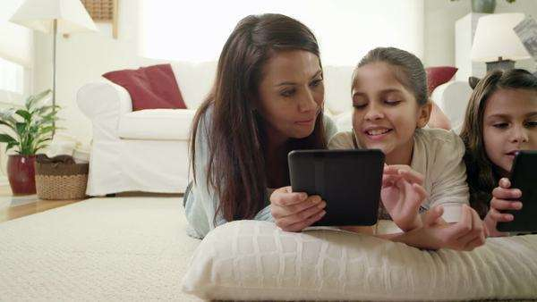 A mother and her two daughters lay on the floor and read from a tablet Royalty-free stock video