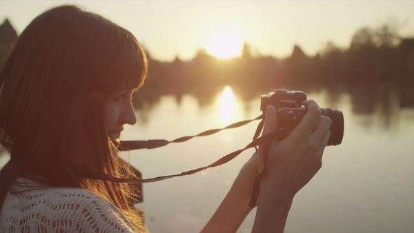 Close up of a young woman taking pictures with her camera at sunset Royalty-free stock video