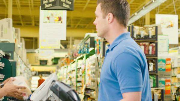 Young happy couple go through checkout line and buy groceries Royalty-free stock video