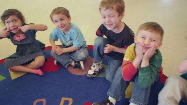 A group of younger children sit in a circle on the floor making funny faces Royalty-free stock video