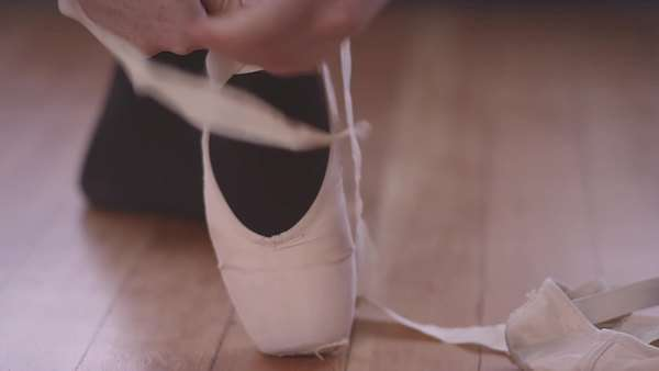 Close-up of a ballet dancer tying up her ballet shoes Royalty-free stock video