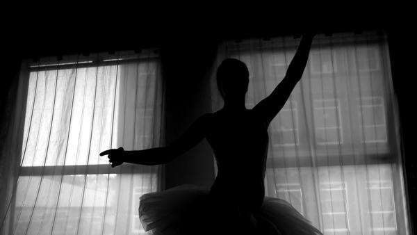 Black and white silhouette of a ballerina dancing in front of a window Royalty-free stock video