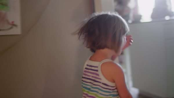 Camera following a cute little girl running through the house in slow motion Royalty-free stock video