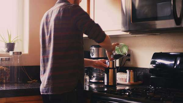 A young man pouring coffee beans into a coffee grinder in his kitchen Royalty-free stock video
