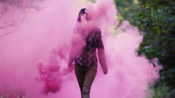 Beautiful young woman in a forest spins around while holding a pink smoke grenade, slow motion Royalty-free stock video