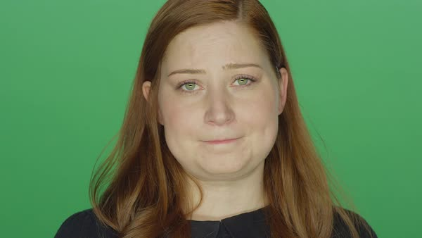Young redhead woman looking sad, on a green screen studio background  Royalty-free stock video