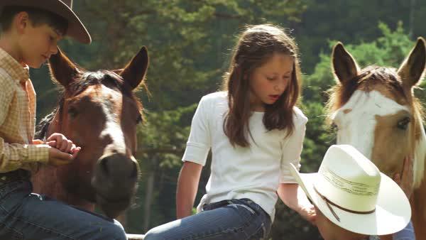 774cc1319 A boy in a cowboy hat sit on a fence with a young girl taking off ...