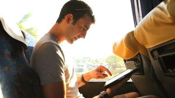 A young man looks through his tablet as he takes a bus ride Royalty-free stock video