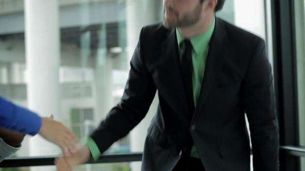 Two coworkers shake hands after a business meeting Royalty-free stock video