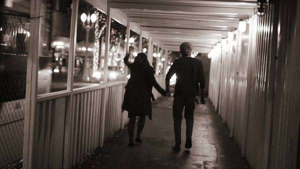 A couple holds hands as they walk down a tunnel at night in the city. Royalty-free stock video
