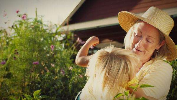 A little blonde girl runs to her grandmother's arms in a garden. Royalty-free stock video