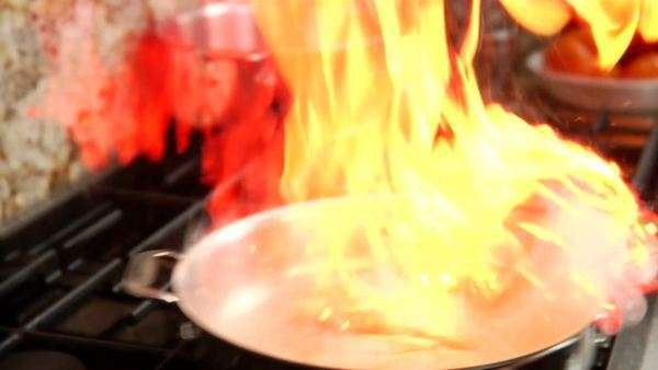 A chef adds some wine to a pan with chicken and flames flare up Royalty-free stock video