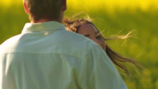 A young couple in love hug and spin around in a open field with yellow flowers Royalty-free stock video