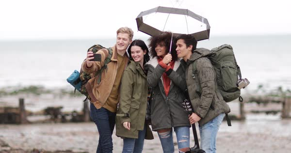 Group of young adult friends taking a selfie on a beach in winter Royalty-free stock video