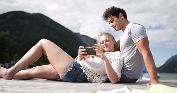 Couple relaxing on dock looking at smartphone Royalty-free stock video