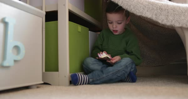 Preschool boy playing with smartphone in den Royalty-free stock video