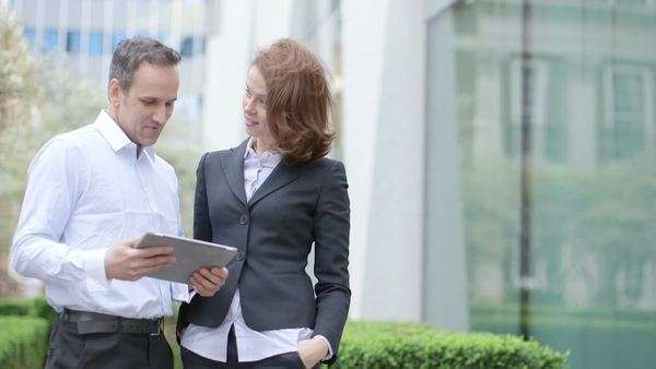 Business man and business Woman discuss plans with ipad, medium shot Royalty-free stock video
