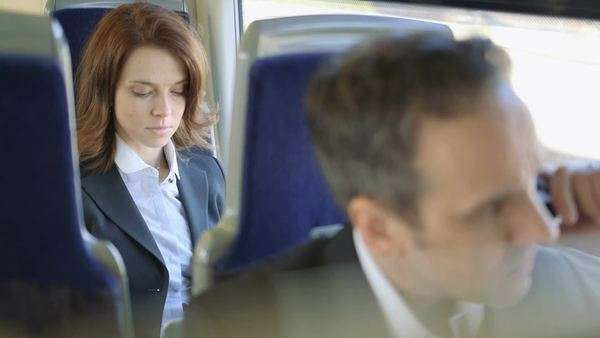 Business man woman sit on a train travelling into the city, medium shot Royalty-free stock video