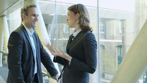 Business man and woman stand on footbridge making plans, medium shot Royalty-free stock video