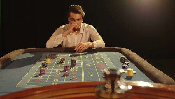A Young Man sips his drink at the Roulette Table, medium shot Royalty-free stock video