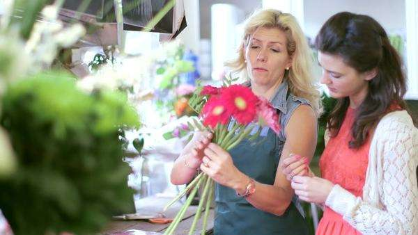 A keen Florist shows a Young Apprentice how to gather flowers into a bouquet, medium shot Royalty-free stock video