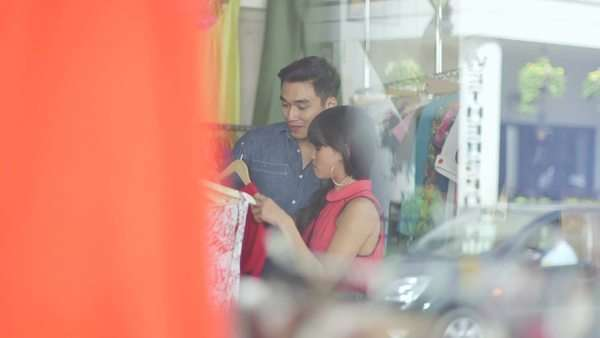 Medium long shot Through Glass A Young Woman and Young Man browse clothes in a vintage store Royalty-free stock video