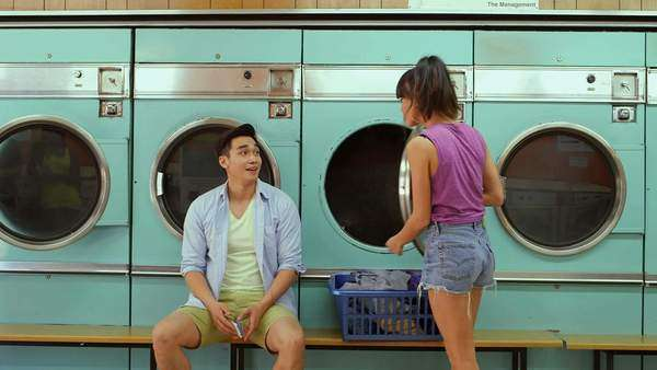 A Young Man and a Young Woman meet in a Launderette, medium long shot Royalty-free stock video