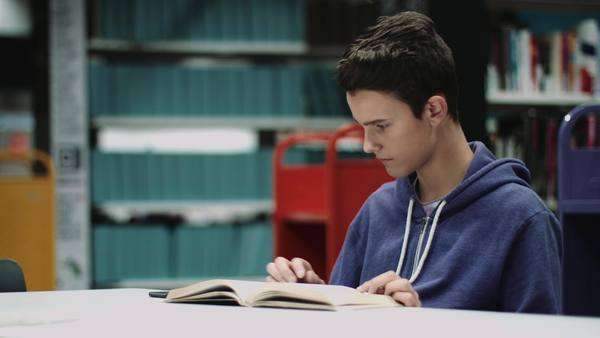 Teenage boy studying book in library Royalty-free stock video