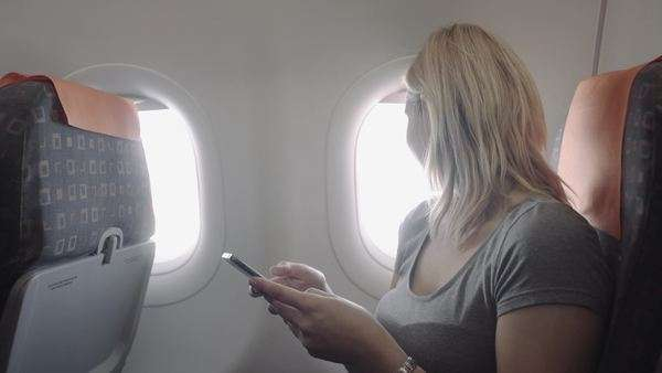 Single young woman on plane with smart phone technology Royalty-free stock video
