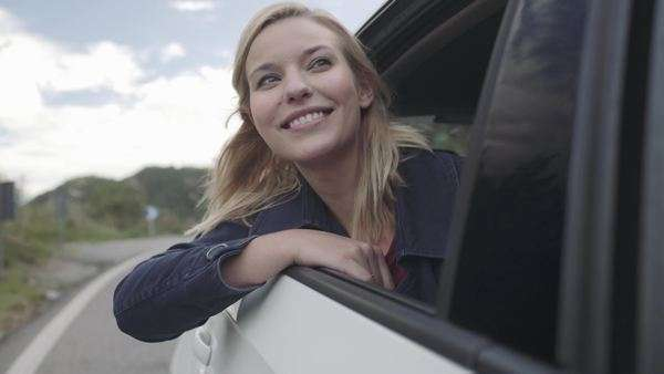 Young woman hanging out of car window enjoying fresh air Royalty-free stock video