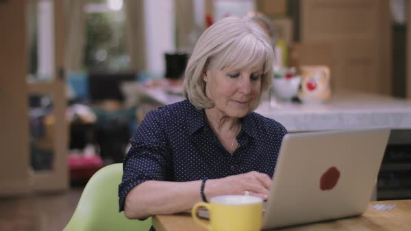 Senior woman buying online using laptop on kitchen table Royalty-free stock video