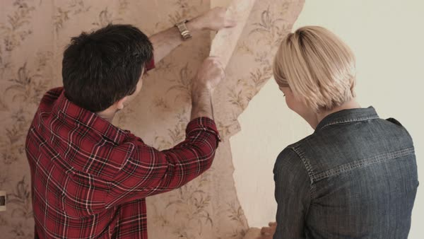 Adult couple home improvement taking of wallpaper Royalty-free stock video