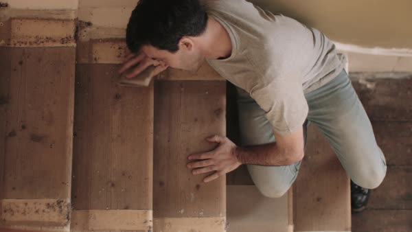 Adult man sanding wooden staircase in new home Royalty-free stock video
