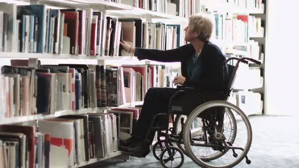 Senior adult woman in wheelchair in library Royalty-free stock video