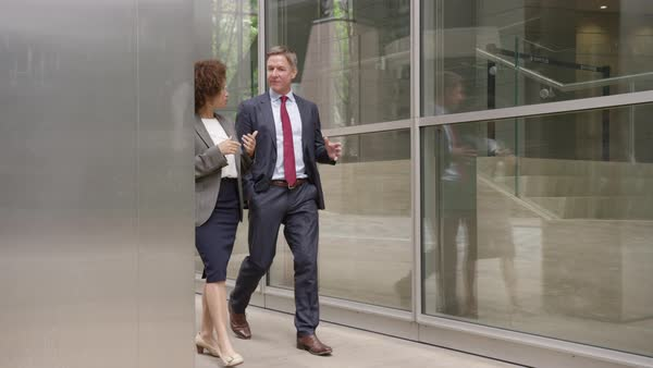 Businessman and businesswoman discussing work on the move Royalty-free stock video