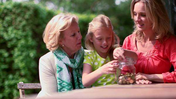 Girl filling coin jar with grandmother and mother Royalty-free stock video