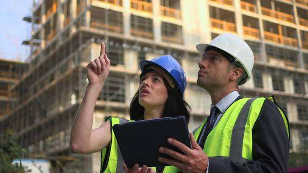 Man and woman discussing with digital tablet at construction site Royalty-free stock video