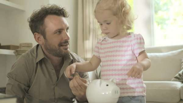 Father helping daughter to save money in piggy bank Royalty-free stock video