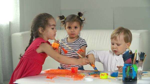 Three kids drawing and smudging finger paint on canvas Royalty-free stock video
