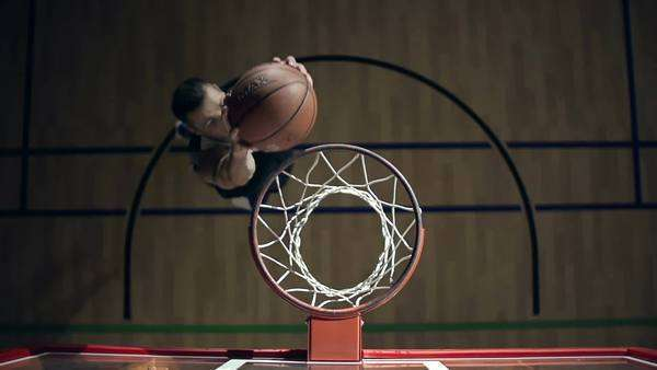 Right from above view of the basketball player dunking the ball through a hoop and hanging on it for a while Royalty-free stock video