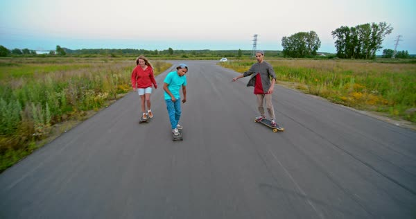 Three teenagers having fun riding their longboards Royalty-free stock video