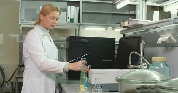 Woman in lab coat looking at tubes with chemicals and making some notes  Royalty-free stock video