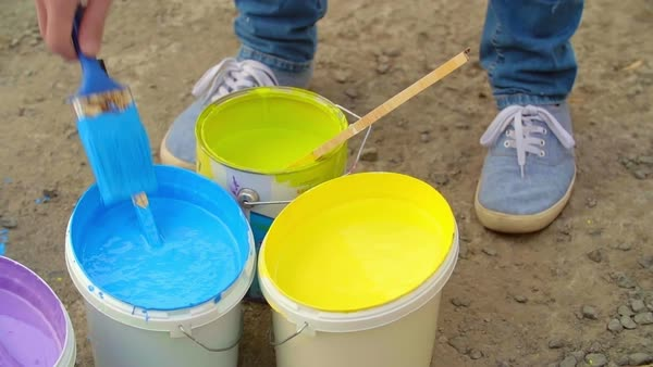 Hand of painter dipping a brush into a bucket with blue paint surrounded by other colors Royalty-free stock video