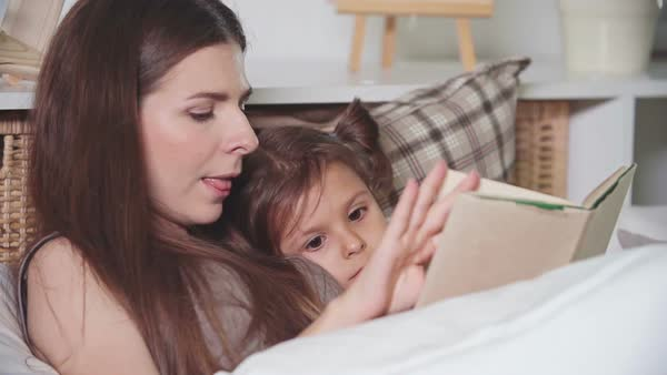 Young mom reading her daughter fairy tale before sleeping Royalty-free stock video