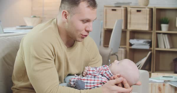 Young father holding his little baby on knees and telling him something funny Royalty-free stock video