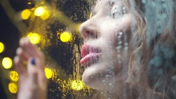 Close up of sad girl looking away and leaving kiss on wet window Royalty-free stock video