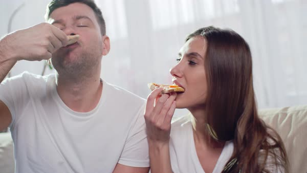 Beautiful couple enjoying pizza together while sitting on the couch and bonding Royalty-free stock video