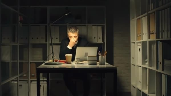 Businessman sitting alone in dark office, signing documents and ...