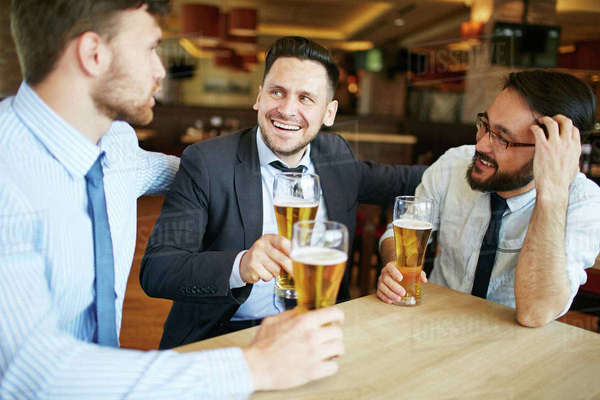 Shot of two Caucasian and one Asian business partners in formal attire laughing and enjoying beer in bar after work Royalty-free stock photo