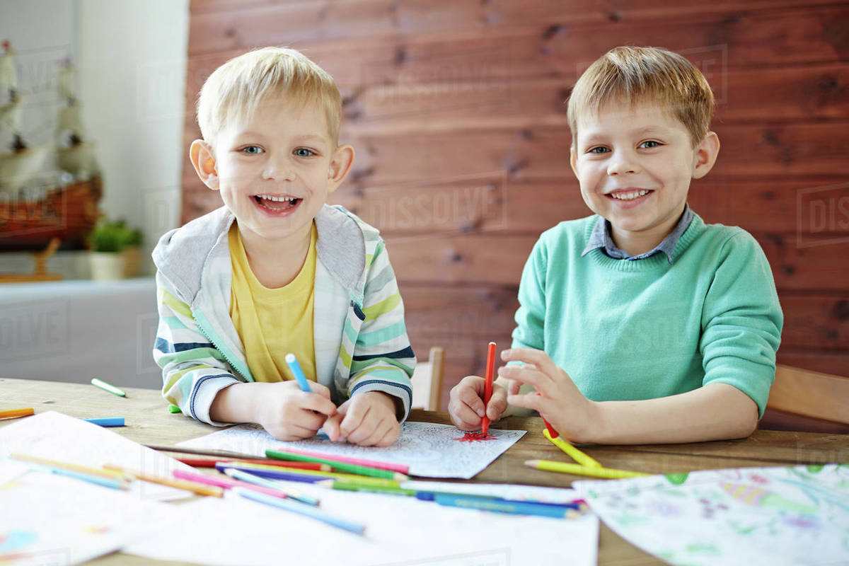 Two happy boys drawing with highlighters